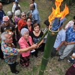 FILE - Irene Perez Ploke Sgambelluri-Beruan, dressed in pink, and others light a torch during a memorial service at the Manenggon Memorial Foundation Peace Park in Yona on July 7.