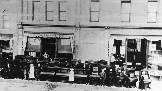 The F. T. Williams Piano  Co. on Main Avenue. The man on the far right is Frank Thomas Williams. There are new pianos on the sidewalk outside of the store.