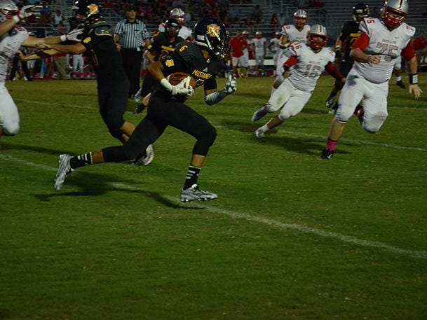 Cameron Latham of Merritt Island is pursued by a host of Satellite players.
