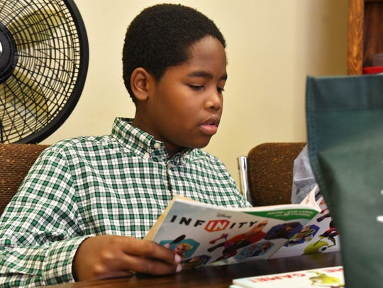 Erique Ray, 11, checks out some of the books available.