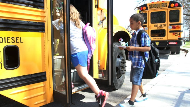 Students board a Springfield school bus at Cowden Elementary in April 2014. The school board has approved expanding the number of students eligible to ride the bus, along with related changes to school start times.