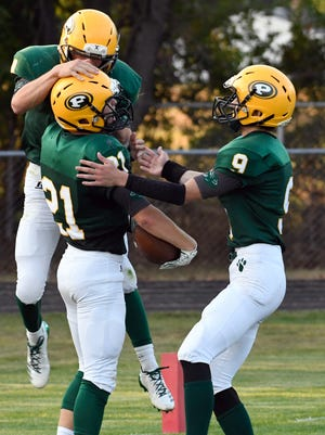 Pennfield teammates celebrate with RB Grant Petersen after scoring the opening touchdown Friday night.