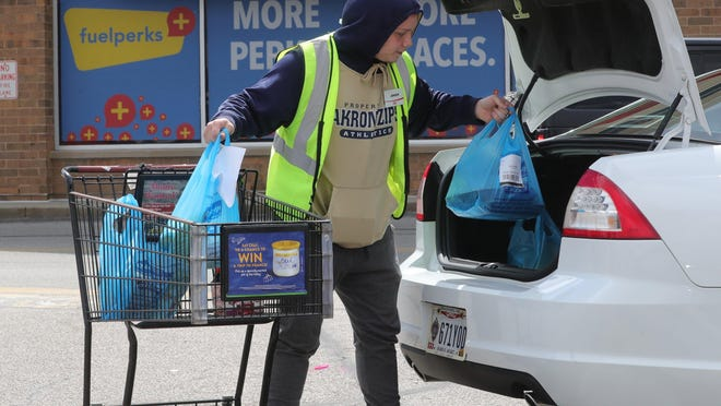 Giant Eagle employee Jensen Barkman loads bags of groceries into the trunk of a car on Howe Avenue in Cuyahoga Falls. The shopping plaza that holds the store just sold for $46 million.