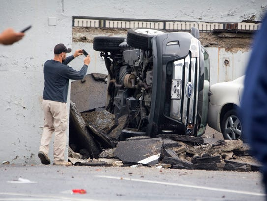 An man inspecting the scene takes photos after a parking