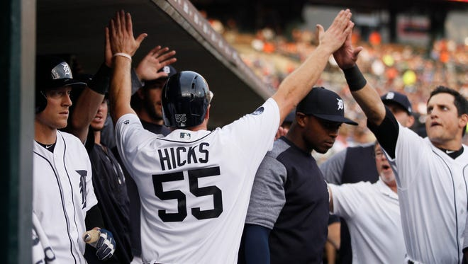 John Hicks is congratulated in the dugout after scoring against the Pirates in the second inning at Comerica Park on Aug. 9, 2017.