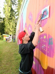 Dennis Decker, 17, paints a portion of the mural taking shape in Poulsbo on the side of the city's Public Works building.