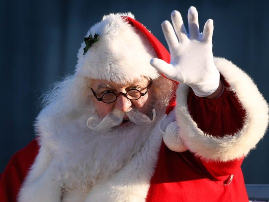 Santa waves to the hundreds lining the street as he