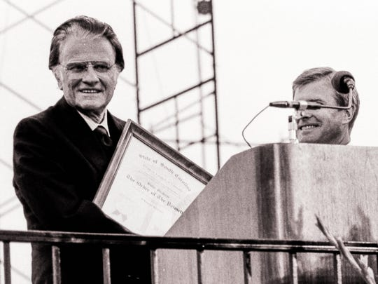 Rev. Billy Graham, left, is given The Order of the Palmetto from Gov. Carroll Campbell, right, during a crusade on April 25, 1987 in Williams Brice Stadium in Columbia.