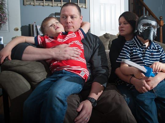 Kelly and Ryan Sexton interact with their two sons, 5-year-old Logan,  left, and 6-year-old Dylan, right. The brothers share a recently discovered genetic disorder called MED13L syndrome. About 10 other children worldwide are known to have the genetic disorder, but there are likely many others.