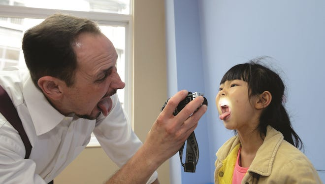 A health care professional checks the throat of a patient at a Sanford World Clinic in Kunming, China.