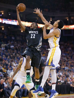 Minnesota Timberwolves forward Andrew Wiggins (22) lays up a shot past Golden State Warriors guard Shaun Livingston, right, during the first half of an NBA basketball game Tuesday, April 4, 2017, in Oakland, Calif.