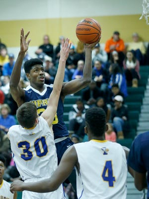 University Prep's Jeenathan Williams jumps over Irondequoit's Zachary Stenglein in the first quarter of a game at Rush-Henrietta High School last season.