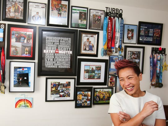 Kathy Nguyen stands in a bedroom of her family's Newark home where one wall is dominated by photos, medals and other mementoes of races run and won.