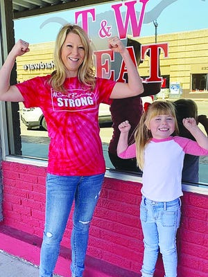 Erin Kirby of T&W Meat in Pratt shows her muscles (along with daughter Tenley) and support for the #SmallBusinessStrong initiative by wearing a #Small Business Strong t-shirt. The shirts, available for purchase at Pratt's Creative Memories, are part of a fund-raising effort among several small businessses in Pratt.