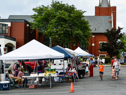 A family checks out the produce and local items for sale at the Downtown Marion Market on Thursday in the parking lot of the Prospect Street United Methodist Church.
