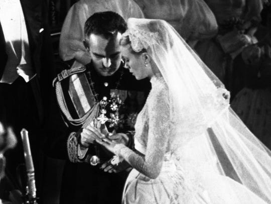 Prince Rainier places the ring on Grace Kelly's finger