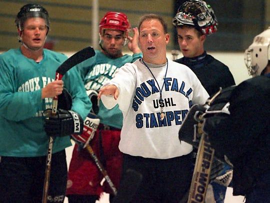 Bob Motzko talks to players at a hockey camp leading