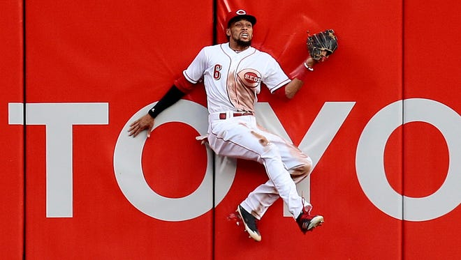 Cincinnati Reds center fielder Billy Hamilton (6) bounces off the right-center field wall as he catches a deep fly ball off the bat of Milwaukee Brewers right fielder Domingo Santana (16) in the top of the second inning.