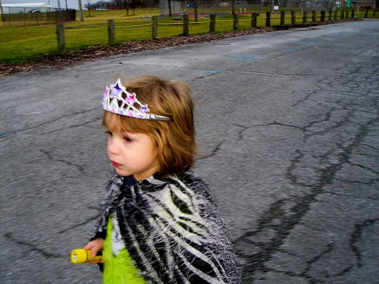 """Zay, 4, wears a cape her aunt made her and a tiara to play at the neighborhood playground with her grandparents. """"She was struggling with what pronouns to use,"""" said Kit Crawford, Zay's grandmother, """"I asked Zay and she sweetly replied, 'She'. And that settled that."""""""