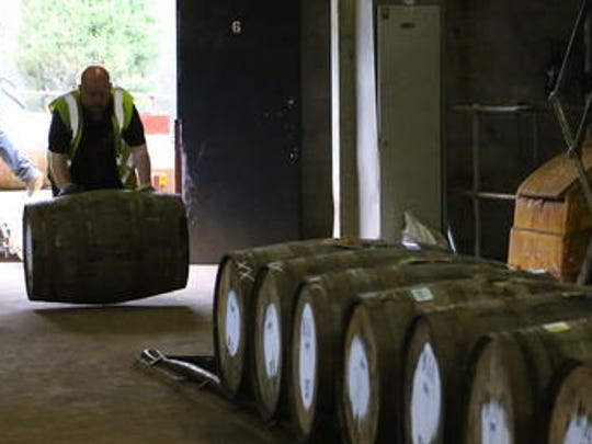 In this photo taken June 30, 2016, a worker rolls in a barrel of whisky at The Macallan distillery in Craigellachie, Scotland. The distillery, famous for its single-malt whisky offers a detailed tour explaining what goes into making the product.