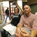 In this Tuesday, Oct. 20, 2015 photo, Carolyn Reilly, left, records the Franklin county Board of Supervisors meeting as her husband, Ian, listens in Rocky Mount, Va. The Reilys left Florida and moved to Virginia in 2010 to farm a 58 acres. Then a year ago, they learned a natural gas pipeline would slice through their farm and their lives took another turn - to activism against the plan. (AP Photo/Steve Helber)