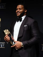 The Rams' Aaron Donald holds his Defensive Player of