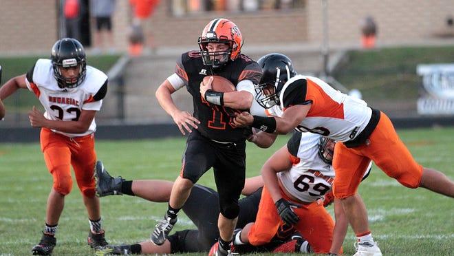Rylee Cain attempts to break free of Dowagiac tacklers in the Trojans' loss to the Chieftains on Friday night.
