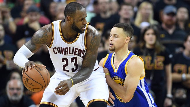 Cleveland Cavaliers forward LeBron James (23) handles the ball against Golden State Warriors guard Stephen Curry (30) during the second quarter in Game 6.