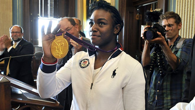 Olympic boxing gold medalist Claressa Shields, of Flint, Mi, shows her London Olympics gold medal as champion of the women's middleweight division  to the applauding Legislators and gallery as she is honored in the Michigan Senate and later  House Chambers in Lansing, MI, in 2012. Shields will headline the Greater Lansing Sports Awards on May 31.