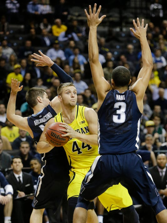 Michigan's Max Bielfeldt (44) looks to pass away from Villanova's Josh Hart (3) during the first half of an NCAA college basketball game Tuesday, Nov. 25, 2014, in New York. (AP Photo/Frank Franklin II)