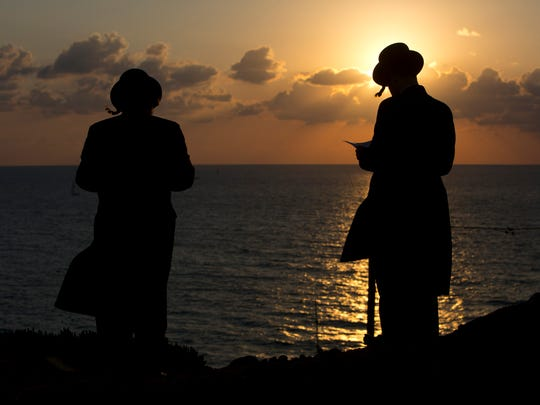 """Ultra-Orthodox Jews of the Hassidic sect Vizhnitz gather on a hill overlooking the Mediterranean sea as they participate in a Tashlich ceremony in Herzeliya, Israel, Thursday, Oct. 2, 2014. Tashlich, which means """"to cast away"""" in Hebrew, is the practice by which Jews go to a large flowing body of water and symbolically """"throw away"""" their sins by throwing a piece of bread, or similar food, into the water before the Jewish holiday of Yom Kippur, which start on Friday."""