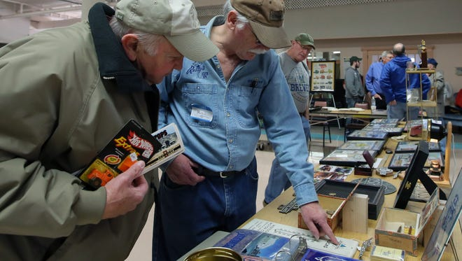 Collector Bill Larson points out and shares history of Oshkosh with people attending the Oshkosh Memorabilia Club show at the Oshkosh Senior Center on March 21, 2015.