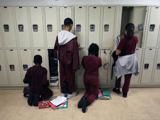 Students tend to their lockers as they change class,