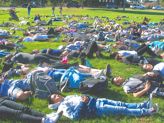 Participants in the third annual Everett Alvarez High School End ALS Run, lie motionless on the grass to identify with the suffering of ALS patients Friday before the run.