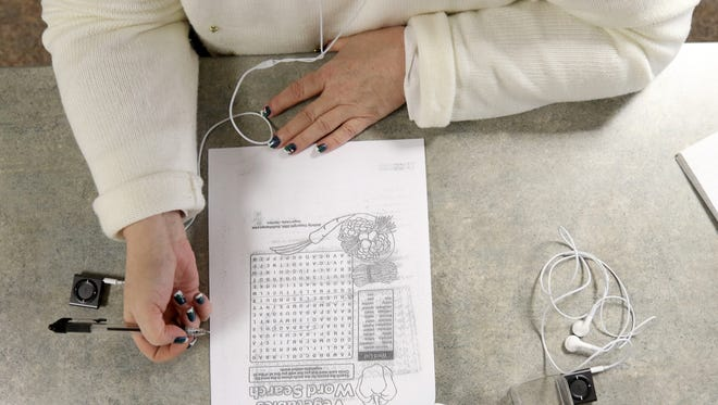 Reporter Karen Madden attempts a simple crossword puzzle while listening to a psychotic voices simulation during a crisis intervention training at Mid-state Technical College in Wisconsin Rapids, Dec. 17, 2016. The point of the simulation is to give officers the experience that someone who actually hears voices would have on a daily basis to help them understand how to respond to people like this.