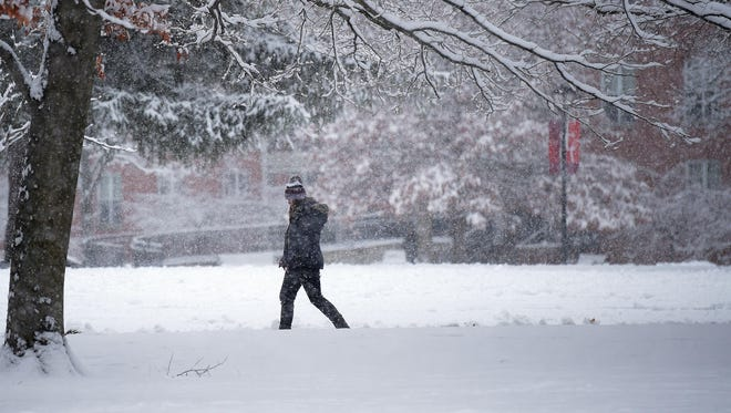 A student walks in the falling snow Dec. 13 at Earlham College in Richmond.