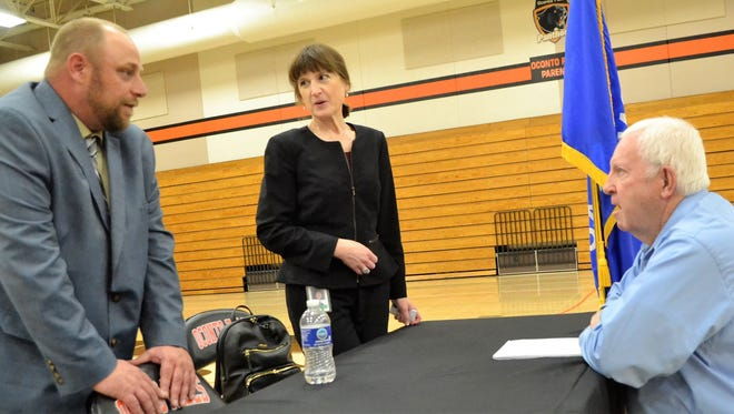Cory Heigl, left, vice president of Packerland Broadband, speaks with Tom Irwin of Madison after a public meeting on broadband service at Oconto Falls High School on May 7. Irwin is working with Langlade County Economic Development Corp. on improving service there. At center is Angie Dickison, the state's broadband director.