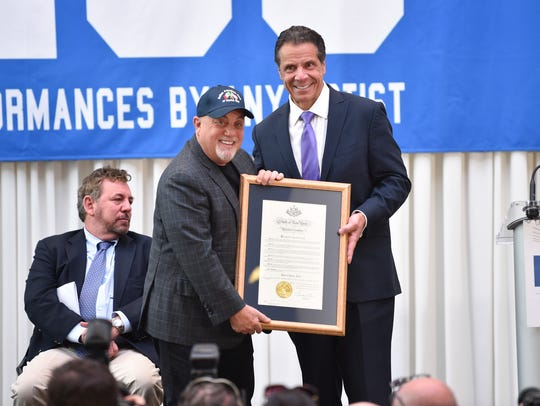 New York Governor Andrew Cuomo, right, presents musician