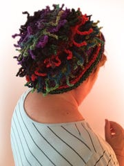 Parson models one of the tendril-covered hats she's