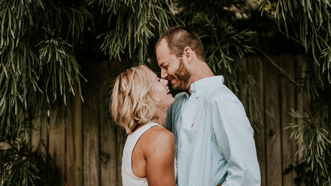 Megan Alexander and Brett Greenhill smile and laugh during their engagement photo session in Atlanta. Greenhill, 39, was paralyzed from the neck down after diving head first into the water, possibly hitting a sandbar, during a visit to the beach in Naples, FL. The couple were in Naples celebrating their joint bachelor-bachelorette parties.