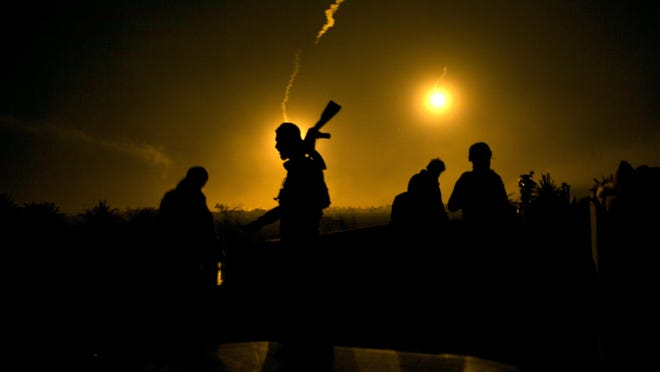 In this Tuesday, March 12, 2019 file photo, a U.S.-backed Syrian Democratic Forces (SDF) fighter watches illumination rounds light up Baghouz, Syria, as the last pocket of Islamic State militants is attacked.