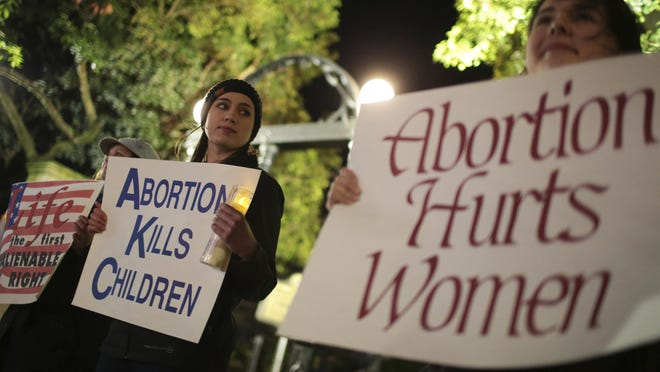 "Ariana Marsh, center, and Katie Davis, right, participate in a pro-life candle light vigil organized by Students for Life at UGA held to protest Roe v. Wade at the University of Georgia Arch, Tuesday, January 24, 2017. Aborion should be illegal and life begins at conception, said Marsh. In the historic 1973 case Roe v. Wade the U.S. Supreme Court declared a pregnant woman is entitled to have an abortion within the first three months of pregnancy without interference by the state. On January 17, 2017, Georgia Representative Jody Hice presented H.R.586 ""To provide that human life shall be deemed to begin with fertilization."" On Monday newly elected President Donald Trump reinstated, the Mexico City Policy. The policy blocked federal funding to non-governmental organizations in foreign countries that perform abortions. In the US, no states receive federal funds for abortions under the the Hyde Amendment. There are exceptions in cases of incest or rape, as well as when a pregnant woman's life is endangered by a physical disorder, illness, or injury, according to the ACLU's website. There are 17 states that do appropriate funds for abortions, the site continues. Roe v. Wade was decided on January 22, 1973."