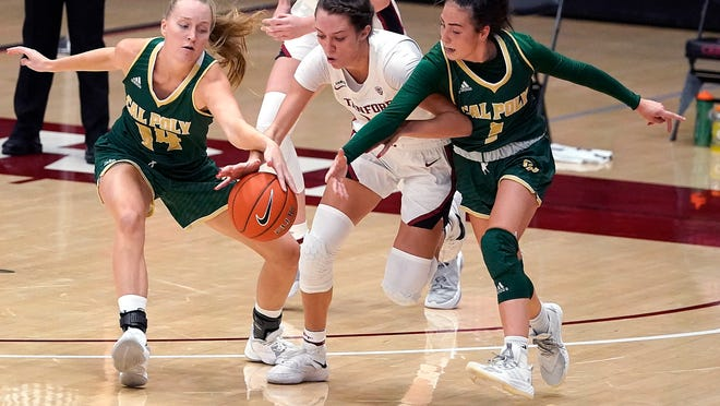 Stanford guard Lacie Hull, center, chases after a loose ball against Cal Poly forward Hannah Scanlan (14) and Abbey Ellis (1) during the first half of an NCAA college basketball game in Stanford, Calif., Wednesday, Nov. 25, 2020. (AP Photo/Tony Avelar)