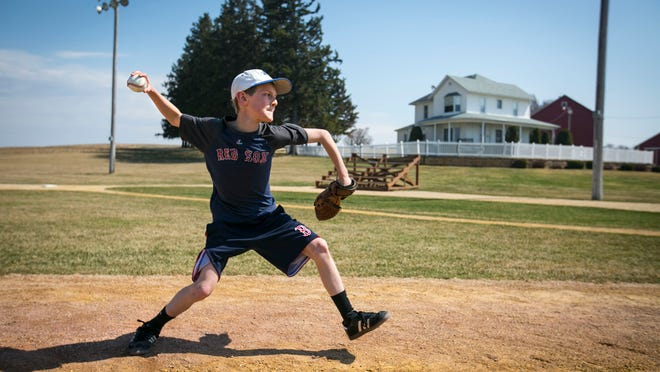 Jackson Brown, 10, of Boston, Mass., pitches to his father Greg, at the Field of Dreams movie site near Dyersville April 12, 2014.
