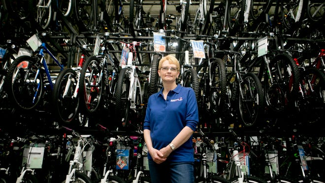 Jenny poses in front of a wall of bikes at Bring's Cycling & Fitness.