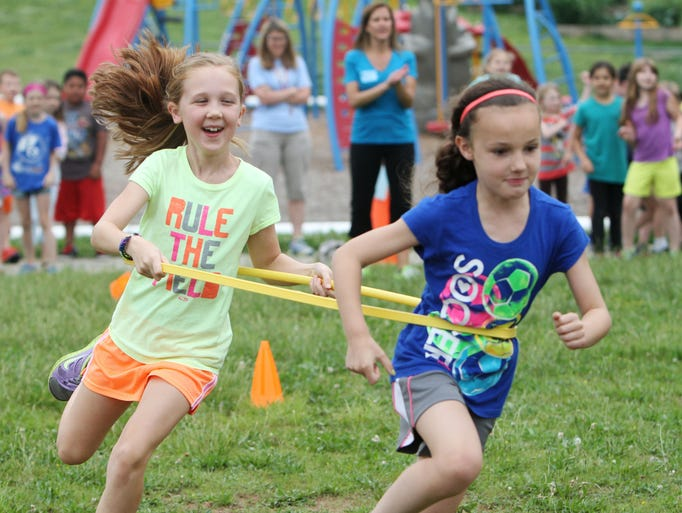 "Madeline Small, left, and Addie Harris run the ""Double Trouble Race"" at Field Elementary's field day on Tuesday, May 27, 2014."