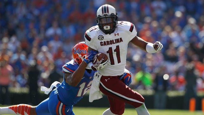 South Carolina Gamecocks wide receiver Pharoh Cooper (11) runs with the ball as Florida Gators defensive back Quincy Wilson (12) defends during the first quarter at Ben Hill Griffin Stadium.
