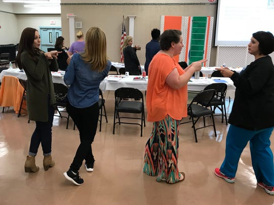 Lexie Leger (left), a special education teacher in Alexandria, Louisiana, and colleagues try some of the music rituals that are part of a program called Conscious Discipline during a training program.