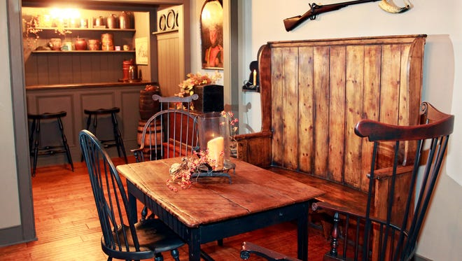 The tavern room has old whiskey kegs and a spittoon by the stand-up bar in the background. A stack of trunks is seen below a painting in the middle of the room. One of the main focal pieces is the antique pine settle bench that is early 1800s flanked by an old pub table in the foreground.