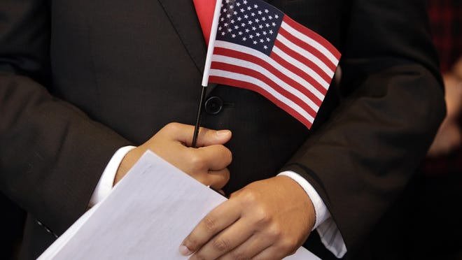 Stallone Laurel Dias, originally of India, and currently serving in the U.S. Army, holds naturalization documents and an American flag during a Naturalization Oath Ceremony, Wednesday, July 18, 2018, at the John F. Kennedy Presidential Library and Museum, in Boston. For many immigrants, the pandemic is a reminder of the separation between loved ones.